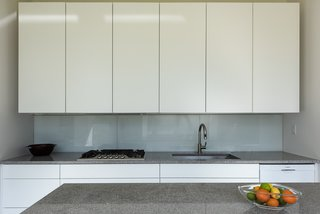 The new, high-end kitchen is a minimalist dream, complete with clean lines, flat-panel doors, and a glass backsplash.