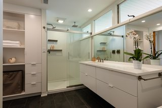 The updated bathrooms are clean and bright. A large mirror sits atop the custom floating vanity.  Clerestory windows allow daylight to enter even the private spaces.