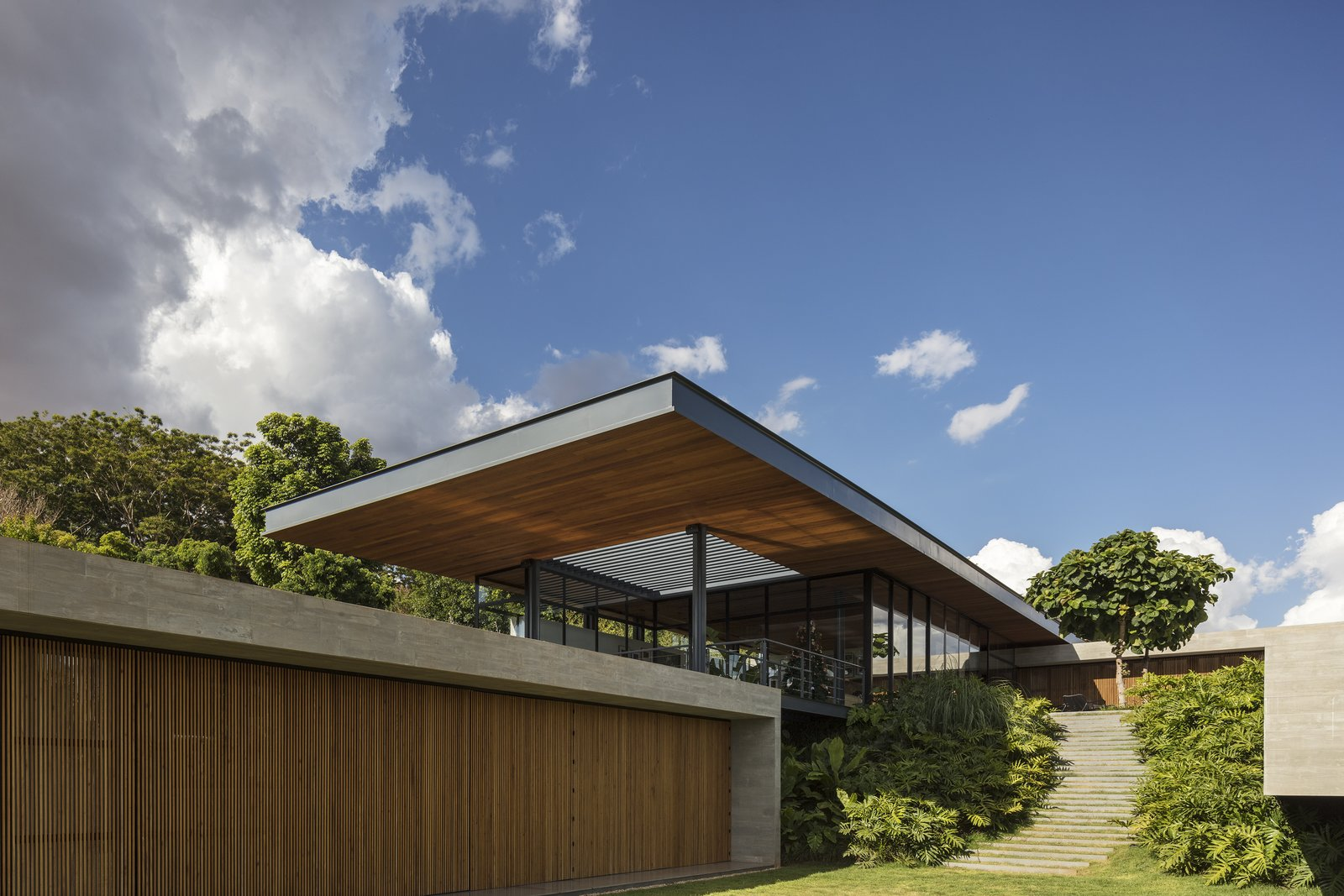 Exterior, Flat RoofLine, House Building Type, Metal Siding Material, Concrete Siding Material, Glass Siding Material, and Wood Siding Material Wood screens provide privacy to the lower level, while allowing for ventilation in this hot, humid climate.   Photo 4 of 12 in A Green Roof Helps Camouflage This Striking Home in Brazil