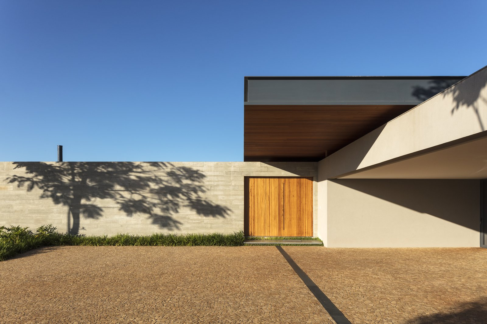 Exterior, Concrete Siding Material, House Building Type, Flat RoofLine, and Wood Siding Material Upon entry, the home appears as simple, solid blocks of concrete with warm, wood accents, hiding the drama and the openness of the opposing facade.   Photo 1 of 12 in A Green Roof Helps Camouflage This Striking Home in Brazil