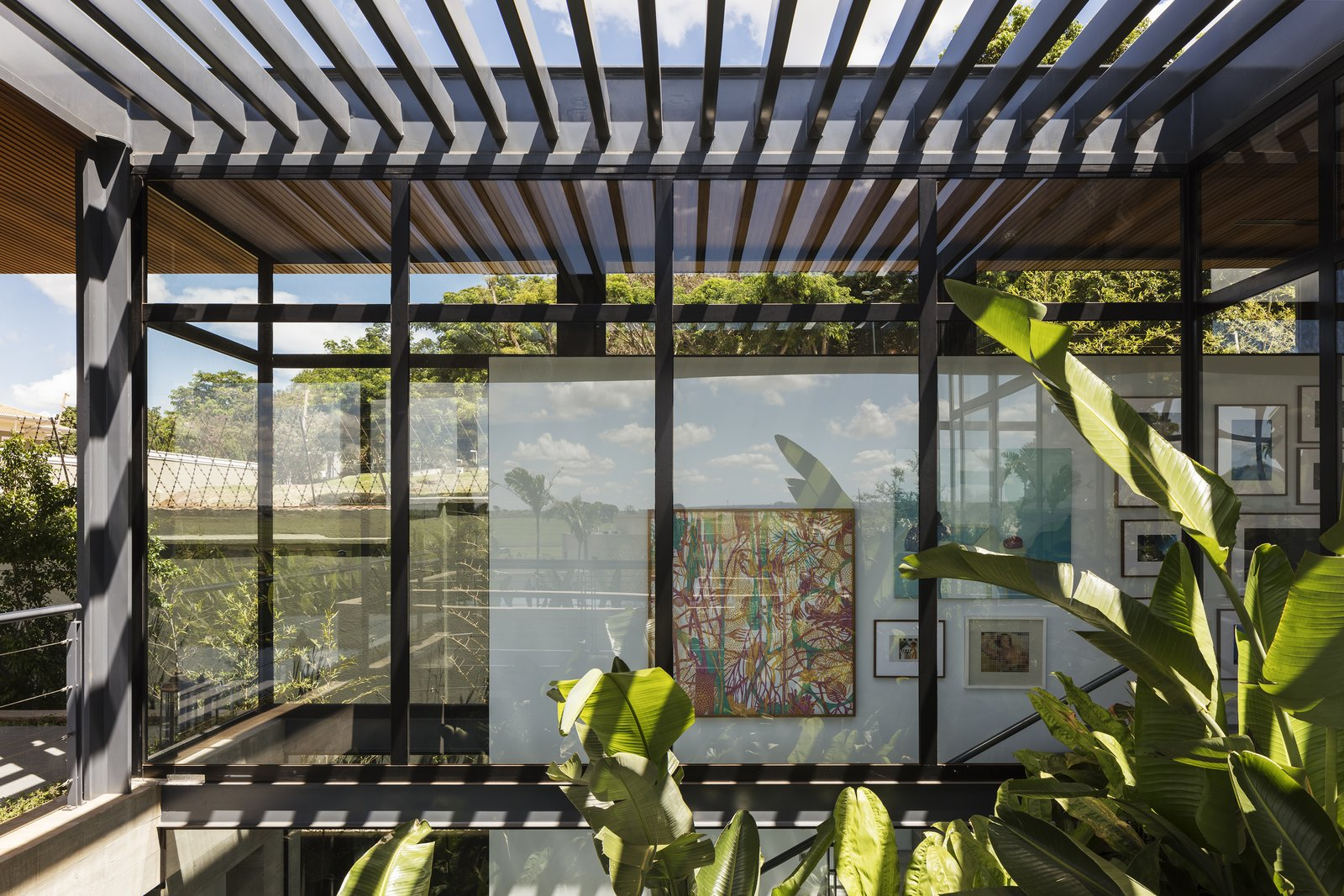 Exterior, House Building Type, Glass Siding Material, Wood Siding Material, Concrete Siding Material, and Flat RoofLine An interior courtyard is covered by trellised shading above, filtering light into the living spaces.   Photo 9 of 12 in A Green Roof Helps Camouflage This Striking Home in Brazil