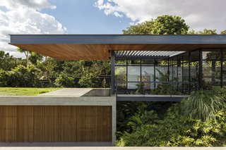 A dramatic cantilevered roof extends over the lower building volume, tying together the separate, yet connected, blocks of the home.