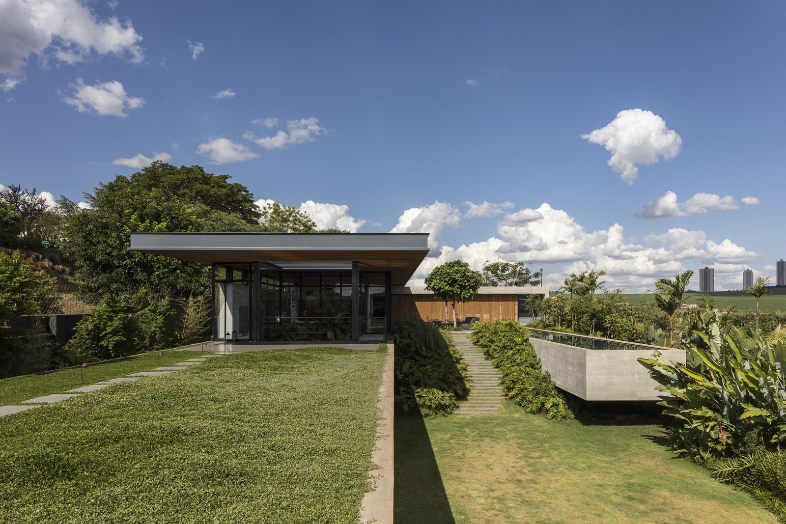 Outdoor, Back Yard, Grass, Trees, Swimming Pools, Tubs, Shower, Concrete Pools, Tubs, Shower, and Gardens Private spaces and sleeping quarters are hidden below the green roof, providing intimate retreats.   Photo 3 of 12 in A Green Roof Helps Camouflage This Striking Home in Brazil