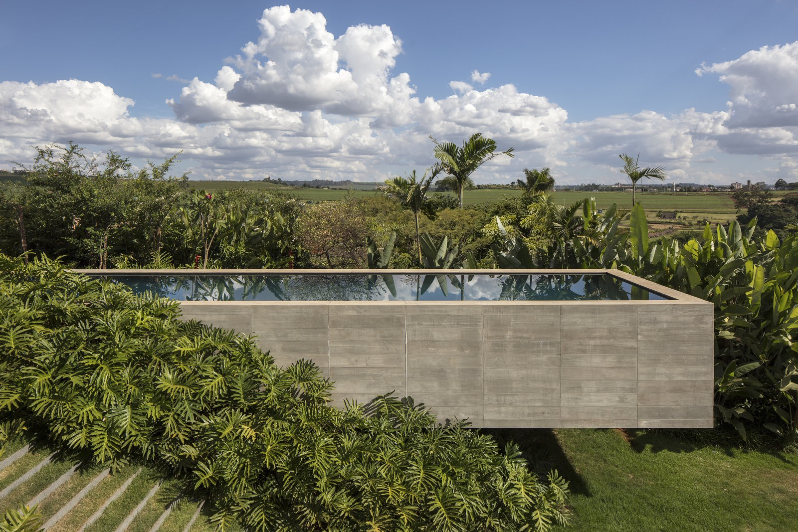 Outdoor, Swimming Pools, Tubs, Shower, Back Yard, Concrete Pools, Tubs, Shower, and Trees Sculptural in form, the concrete faced pool hovers gently above the hillside, while reflecting the sun and clouds as they pass overhead.   Photo 6 of 12 in A Green Roof Helps Camouflage This Striking Home in Brazil