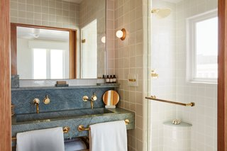 A monolithic, imported stone vanity in the bathroom is accented by brass fixtures and hand-cut and crafted tile.