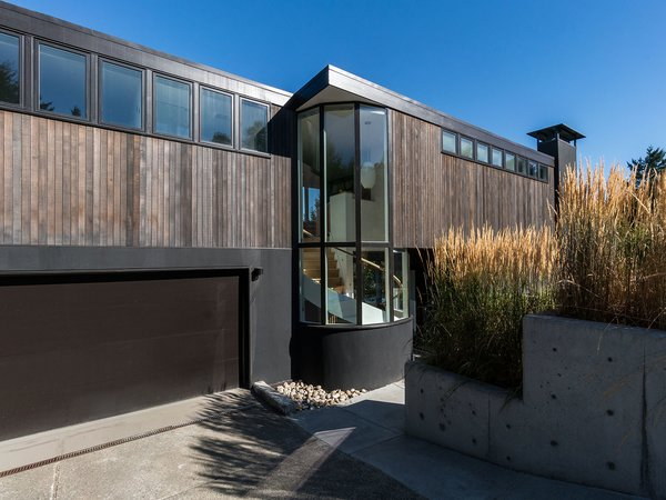 Clad in natural materials, the residence is truly at home in the Pacific Northwest. Tall glazing provides a glimpse inside, with peeks of the elegant, spiral stair.