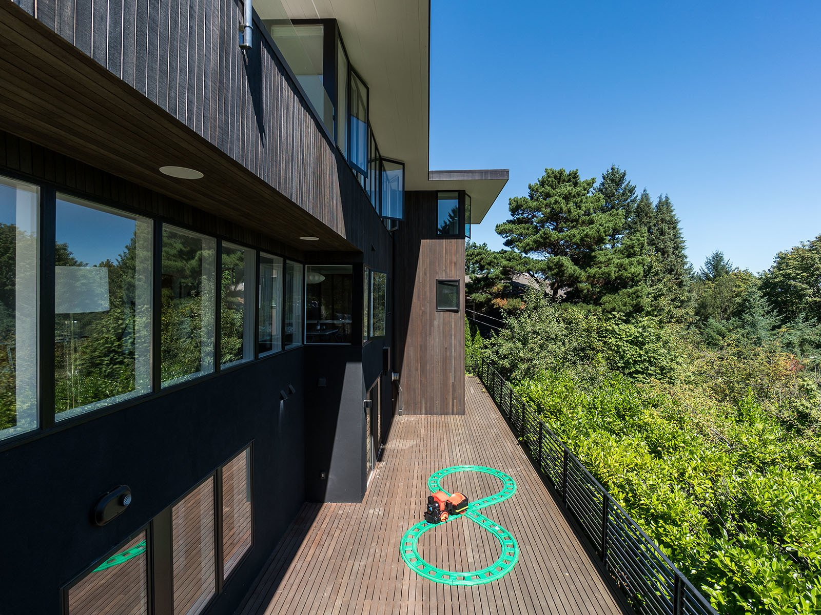 Outdoor, Wood Patio, Porch, Deck, Metal Fences, Wall, Hanging Lighting, Side Yard, Horizontal Fences, Wall, Small Patio, Porch, Deck, and Trees The rear of the house resembles the feeling of a tree house, suspended high up in the trees blending indoors with outdoors.   Photo 20 of 20 in An Iconic Portland Home With Sweeping Mountain Views Asks $1.75M