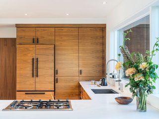 Walnut cabinets and crisp white countertops create a streamlined, modern kitchen.