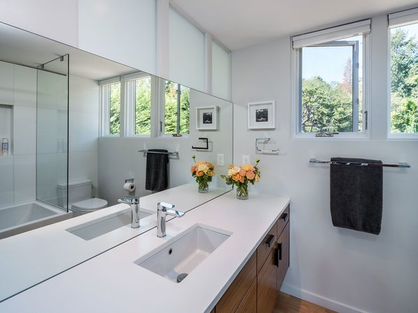In the bathroom, a floating wood vanity adds a simple modern touch. A large, seamless mirror and windows allow daylight to fill this small space.