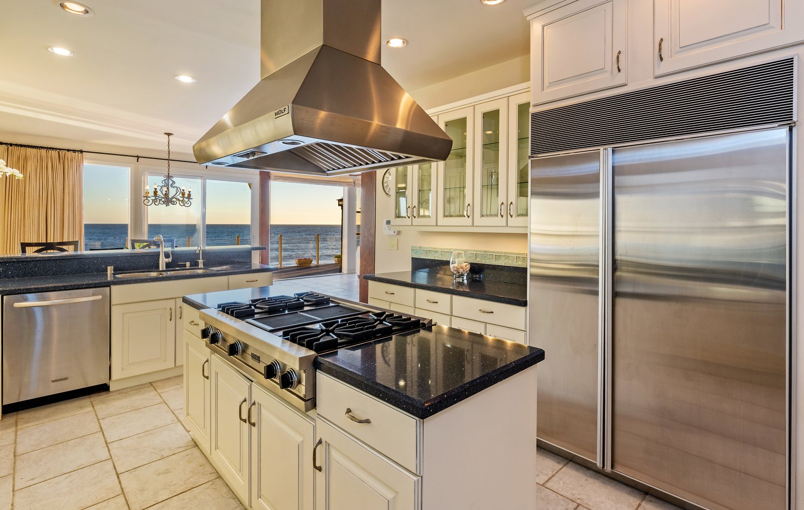 Kitchen, Refrigerator, Ceramic Tile Floor, Cooktops, Range Hood, and White Cabinet The recently updated kitchen includes top-of-the-line appliances and finishes.  Photo 9 of 12 in 'Brady Bunch' Actor Barry Williams Lists His Malibu Home For $6.4M