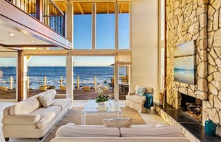 The two-story living space is open to the bedrooms above.  A full-height wall of windows draws the ocean views inwards.