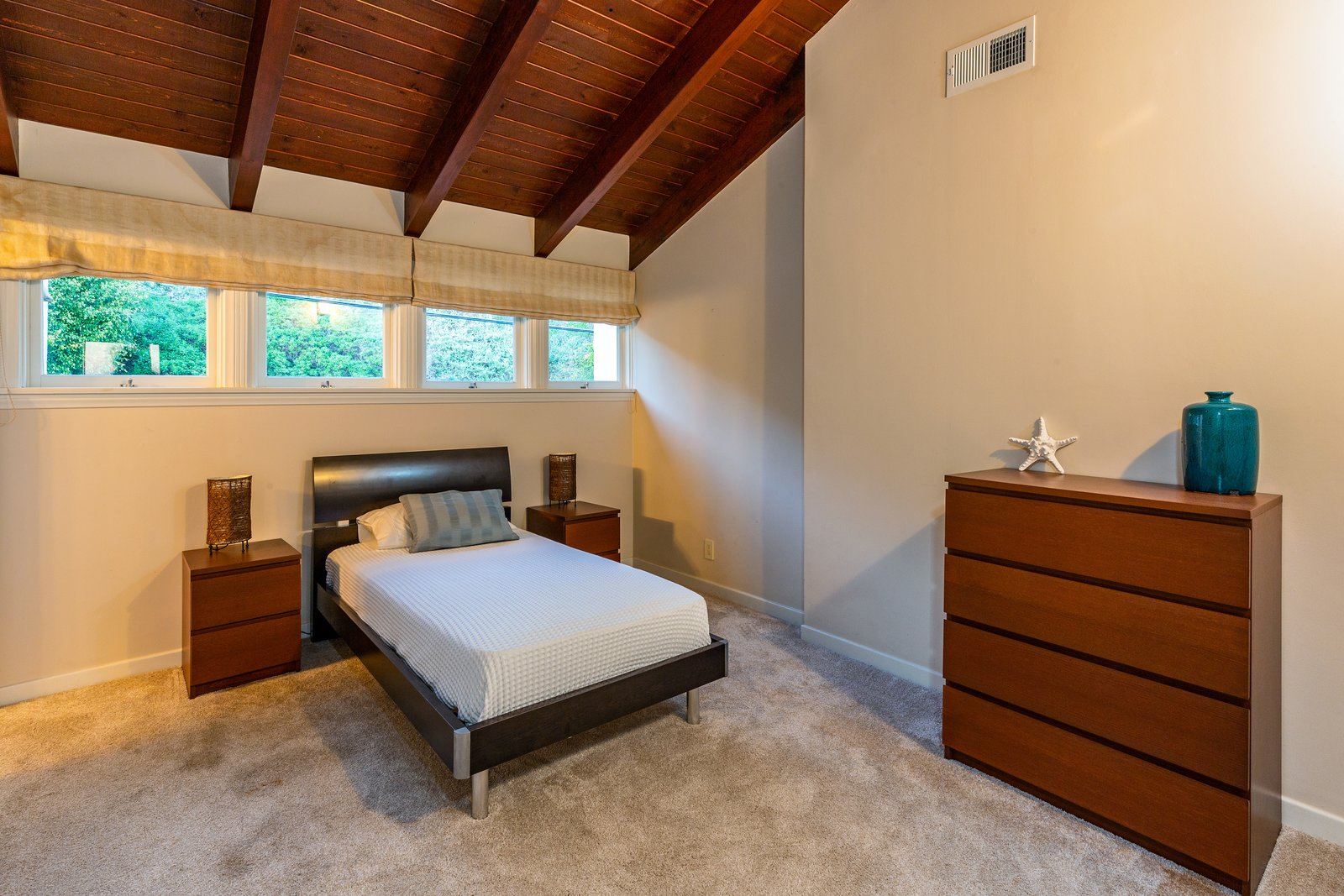 Bedroom, Carpet Floor, Night Stands, Bed, and Dresser The wood-beamed ceilings carry into the additional en-suite bedrooms which feature beach or mountain views.  Photo 12 of 12 in 'Brady Bunch' Actor Barry Williams Lists His Malibu Home For $6.4M