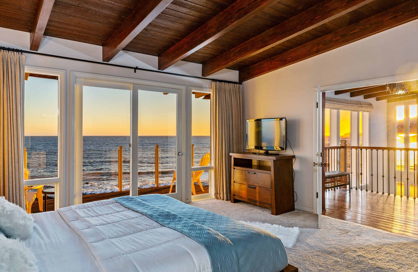 Bedroom, Bed, Carpet Floor, and Dresser The master suite includes two private decks, a fireplace, large closet, updated bath, and wood-beamed ceiling.  Photo 10 of 12 in 'Brady Bunch' Actor Barry Williams Lists His Malibu Home For $6.4M