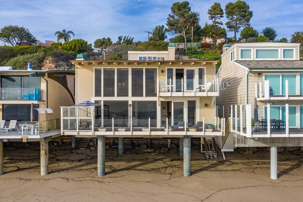 Supported by concrete columns, the home hovers above the sandy  terrain. An expansive ocean-front deck blends indoor and outdoor living spaces.