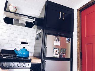 The kitchen is complete with all the cooking necessities—fridge, range, hood—and decorated with modern black cabinets, brass hardware, and butcher block counters.
