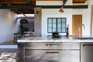 The custom steel kitchen island with a marble top is from Eginstill.
