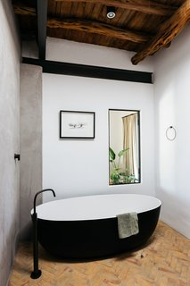 The bathroom blends sleek contemporary fixtures with natural materials. A free-standing black and white tub is surrounded by concrete walls, terra-cotta tile flooring, and an exposed wood ceiling.