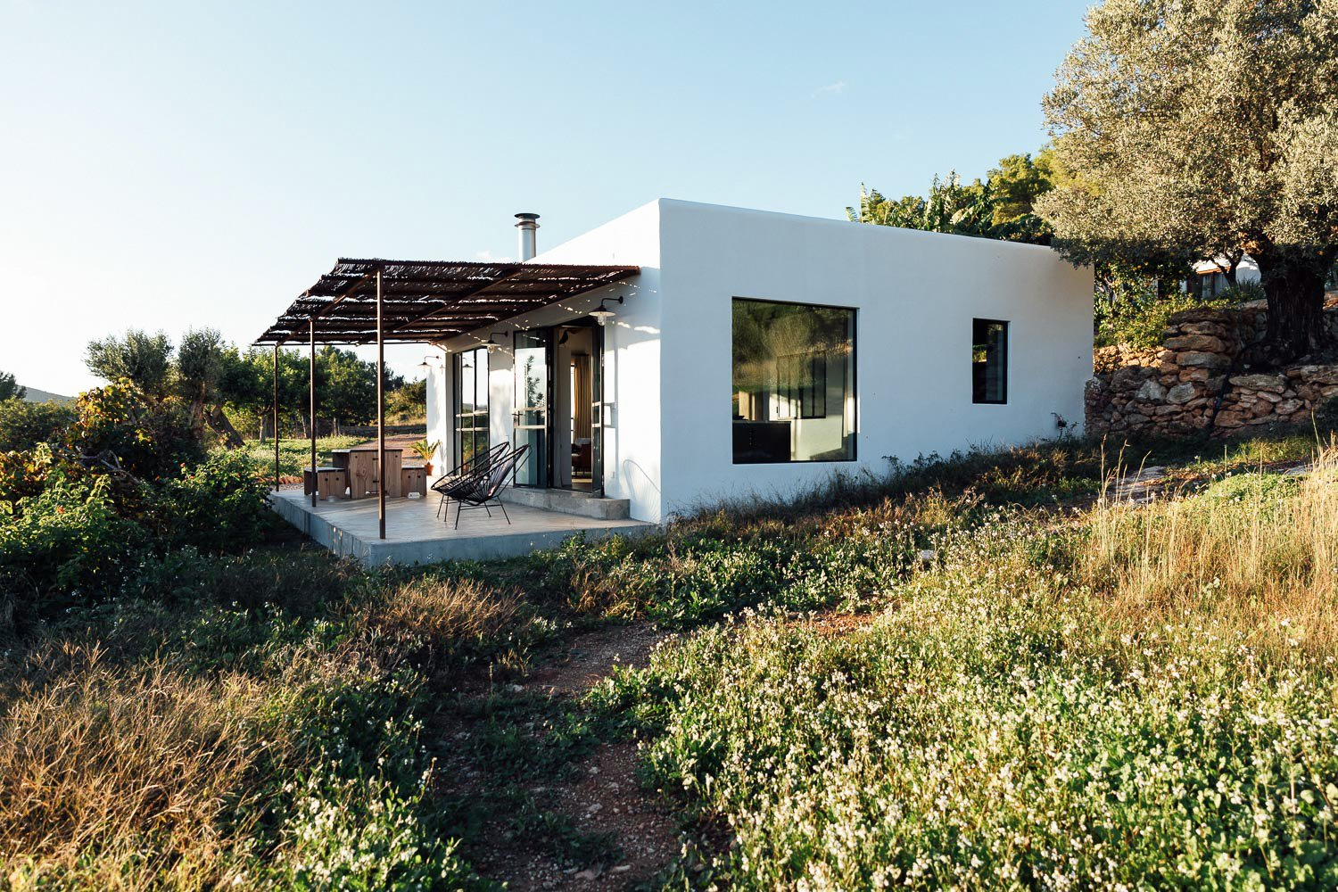 Exterior, Flat RoofLine, House Building Type, Stucco Siding Material, and Tiny Home Building Type Campo Loft is surrounded by lush vegetation atop a mountainous hillside.   Photo 1 of 20 in An Abandoned Warehouse Makes Way For a Breezy Ibiza Retreat