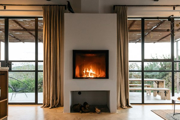 Living Room, Wood Burning Fireplace, Wall Lighting, and Concrete Floor The fireplace is the focal piece of the living area, anchored by glazed openings on either side.  Photo 10 of 20 in An Abandoned Warehouse Makes Way For a Breezy Ibiza Retreat