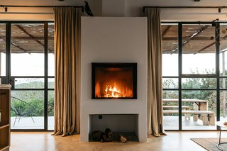 The fireplace is the focal piece of the living area, anchored by glazed openings on either side.
