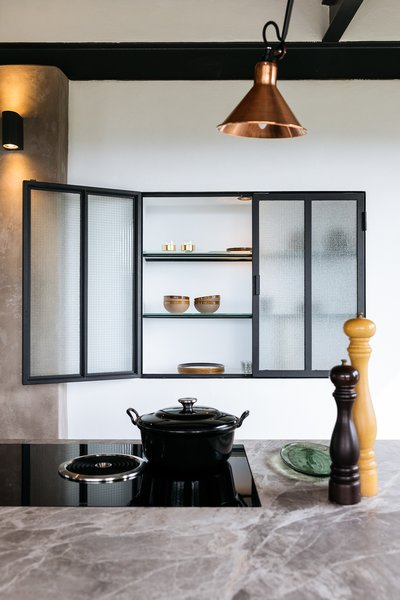 The kitchen is a contemporary installation in a 100-year-old home. A custom, steel-and-glass cabinet is built into the wall for additional storage space, while tying in with the black steel framing above.
