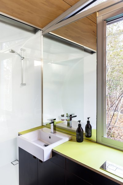 Green linoleum countertops and black cabinets reappear in the bathroom. A south-facing window draws in plenty of natural light. Even the cabinetry and plumbing fixtures were built in the workshop.
