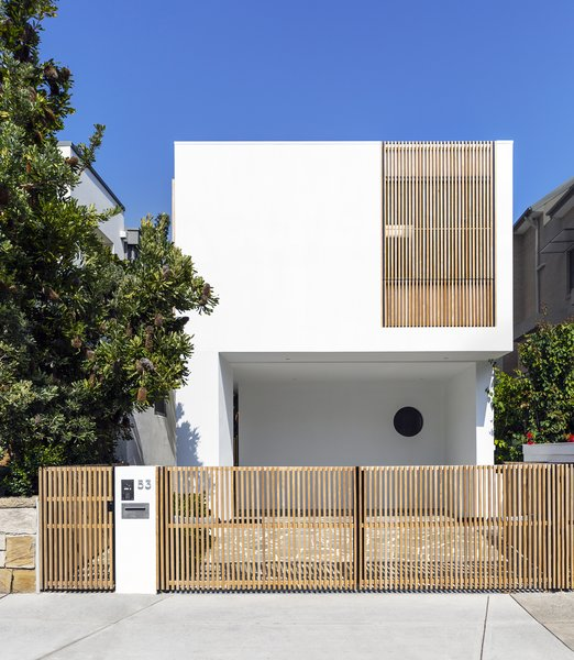 From the street, the house appears as a simple, white structure with timber elements. It's not until you enter that the lightness and porosity of the home becomes apparent.