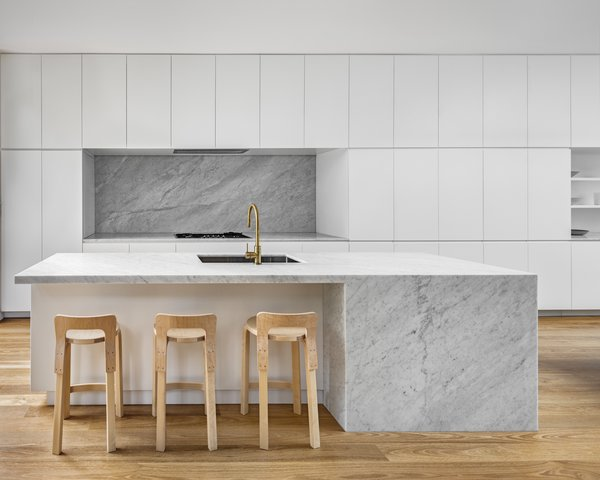 A large, marble island is the focal point of this all-white kitchen, with the marble backsplash helping to tie the space together.