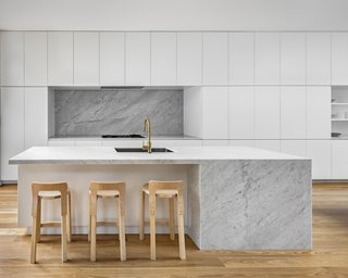 A large, marble island is the focal point of the all-white kitchen.