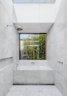 Even the master bath fully embraces the Bondi Beach location.  A large picture window and skylight create the feeling of being outdoors in this marble oasis.