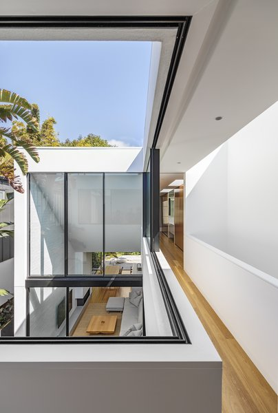 The hallway wraps around the courtyard below. Sliding windows blend the divide between the interior and exterior spaces.