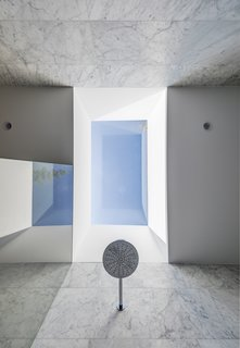 The skylight above provides a rhythm of light and shadow across the shower walls.