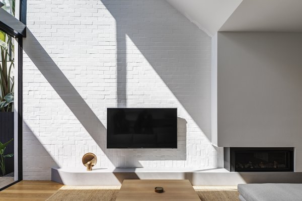White brick walls provide a textured backdrop for light and shadows to play.