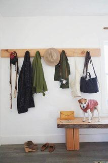 Natural wooden elements, like this custom-made coat rack and 15-foot-long wooden bench, outfit the home.