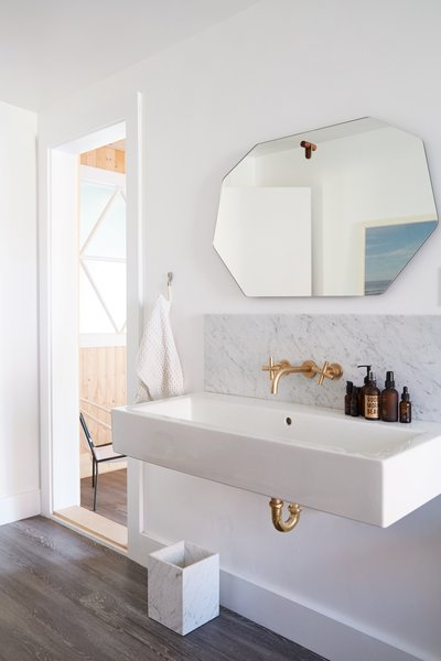 Brass and marble accents, a large wall-mounted sink, and a geometric mirror create a serene bath retreat.