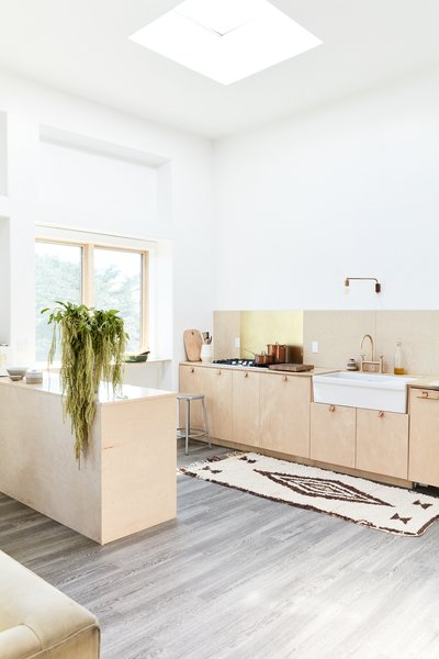 White walls and wood accents create a subdued, relaxing vibe. A skylight draws light into the cooking and living spaces from above, while large windows provide views of the California scenery.