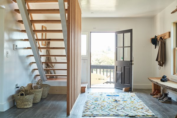Rustic and modern elements create a cozy, cabin feel. The eye-catching wood stair is a focal point upon entry.