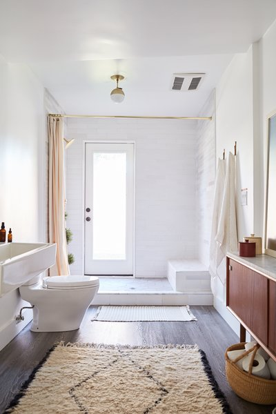 Modern elements blend with rustic materials in the bath, including an open tile shower, marble step, and brass ceiling light from Cedar + Moss.