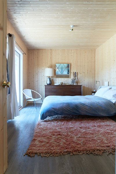 Pine wood paneling wraps the walls and ceiling of the master bedroom.