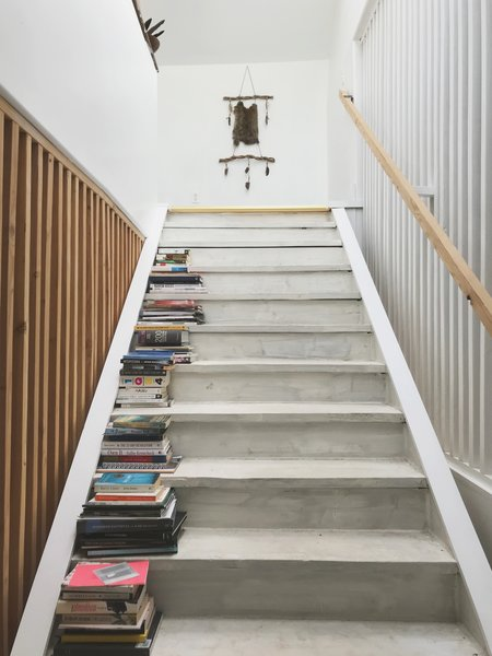 The White Washed Wood Staircase Is Framed By Wooden Slat Walls On Both Sides