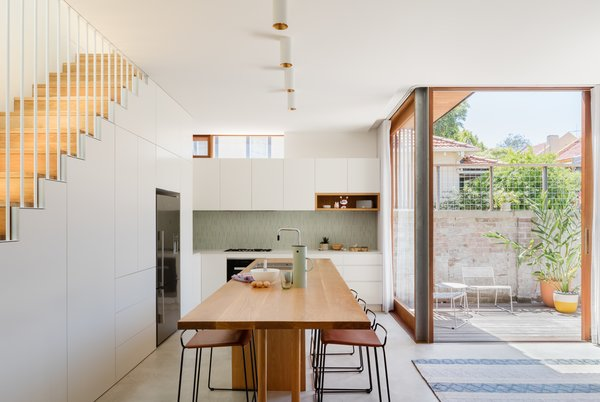 The kitchen cabinets flawlessly fit below the line of the staircase. On the far end, a clerestory window is positioned above the cabinets to draw light into every corner of the living space.