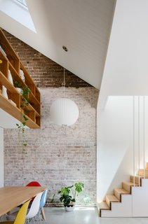 In the dining room and loft space, the original brick wall has been left exposed and raw.