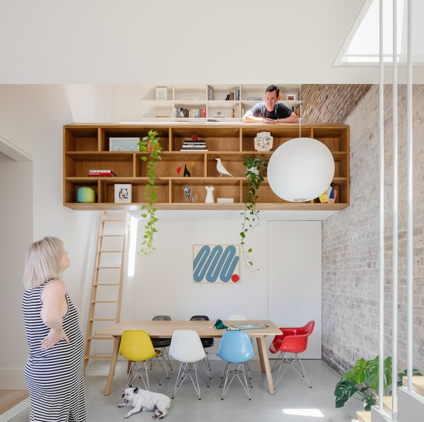A mezzanine loft level provides extra floor space without increasing the home's footprint. Built-in bookshelves double as a guardrail for the lofted work space, accessed by a built-in ladder.