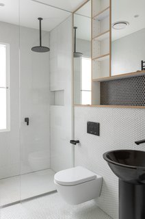 A seamless glass shower screen and matte black fixtures are contemporary additions to this sleek and simple bath.   Custom wood cubbies and penny tile on both the walls and floor add a sense of playfulness and texture to the rehabbed bathroom.