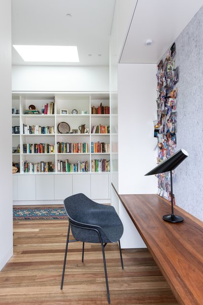 The original cottage has been reimagined to incorporate a study area. A built-in wood desk, felt tack board, and contemporary Ligne Roset desk chair provide an ideal work area.