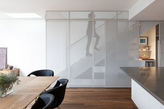 The timber staircase is concealed behind perforated metal screens, with storage below.