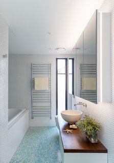 Colorful penny tile in blues and greens decorates the floor in the master bath.  White penny tile wraps the walls, accented by a floating vanity and vessel sink.
