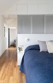 Perforated metal screens connect design elements in the upstairs to the main floor below.  A built-in headboard provides clothes storage on one side, and nightstands on the other.