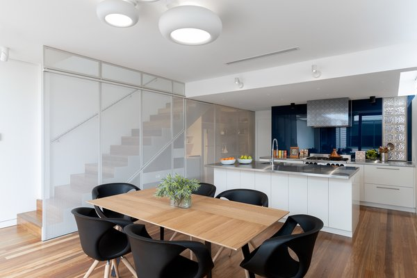 The kitchen was designed to work best for the professional chef with a stainless-steel kitchen island, exposed decorative hood, and plentiful storage concealed behind operable perforated screens.