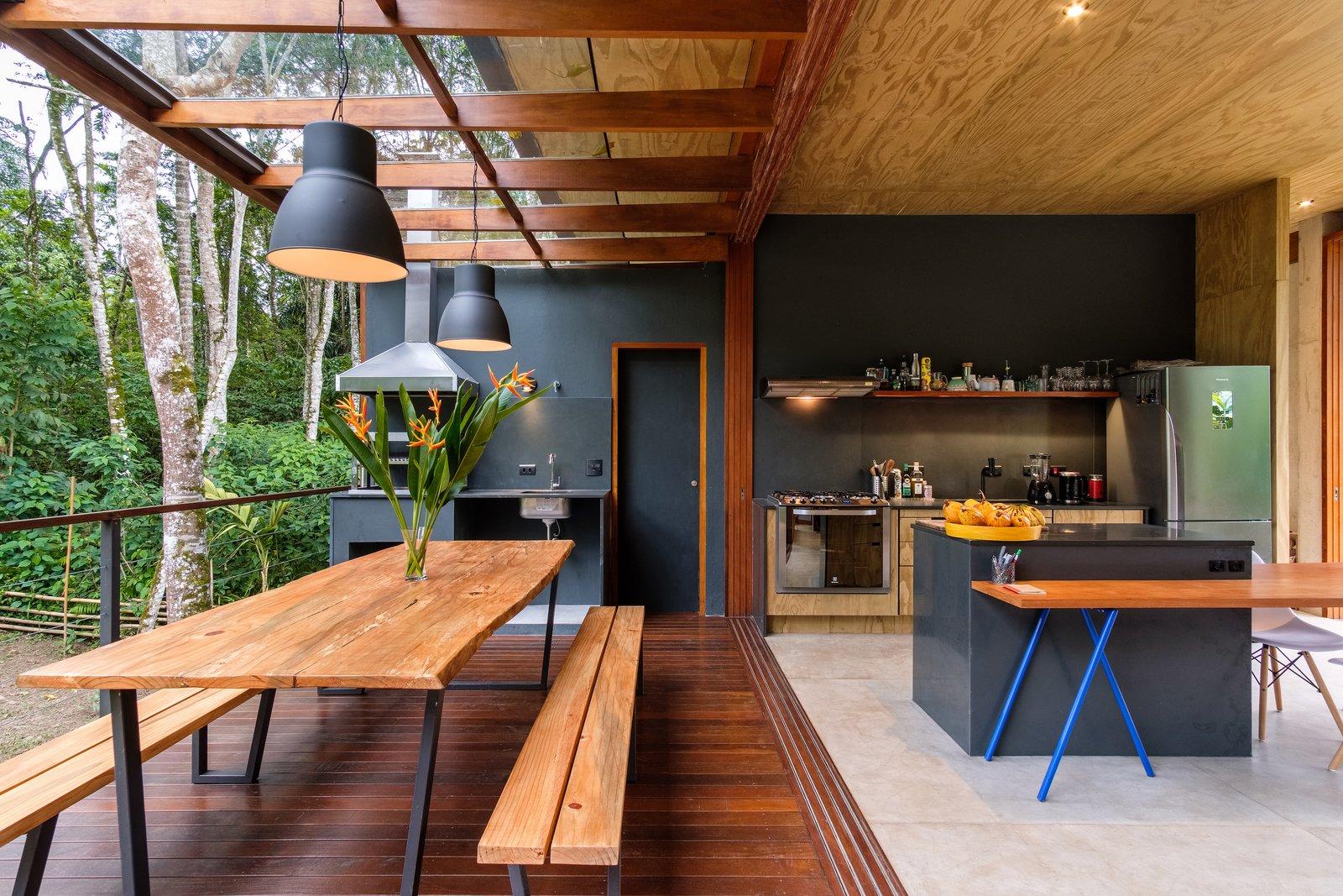 Comedor, banco, piso de concreto, mesa, colgante y piso de madera de tamaño medio Un toldo de madera y vidrio brinda protección sin disminuir las vistas.